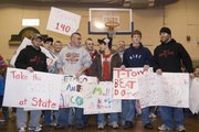 The state-bound Tonganoxie High School wrestlers hold the signs made by the Tonganoxie Elementary School Students at a TES assembly Thursday morning. Left: Jeremy Goeble, THS wrestling coach, Kevin Hamm, junior, Travis Adcox, senior, Cameron Adcox, senior, Wyatt Coffin, senior, Matt Brock, junior, Gene Samuels, assistant coach, Steve Davis, junior, Scott Underwood, assistant coach.