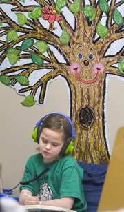 Mize Elementary School second-grader Sarah Knowles was sitting in a quiet section of her classroom with headphones on while working on an interactive book. Sarah is in a reading group based on her skill level and adjustments are made as her needs change.