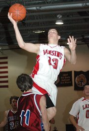 Lansing High senior Bobby Hauver elevates to the basket during Lansing's 58-42 loss to Topeka Seaman in the substate tournament finals. Hauver was called for charging on the play.