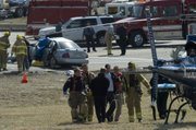 Emergency crews carry an injured passenger to be air lifted to KU Medical Center. A late Friday morning accident involving a 2002 Nissan and a pickup truck was at the intersection of Kansas Highway 32 and the entrance ramp to northbound K-7.