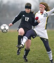 Basehor Linwood junior Jenny Swabb (33) kicks around De Soto junior forward Amber Laudick in first period action Thursday. De Soto won the game 4-3 in overtime.