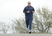 Don Clark crests a hill at Kill Creek Park during a run workout Saturday. Clark, a De Soto Board of Education member, will run in next week's Boston Marathon.