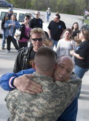 A line of friends and family forms in front of Sgt. Joe Peel to welcome him home.