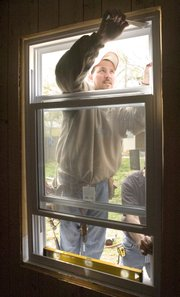 Jimmy Thompson with Sundance Windows helps install one of the 10 new windows on the house at 69th Street Saturday.