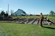 Blake McCall points out where the roof on the ground in front of him used to be before Friday morning's wind storm. The truck and lawn mower that were housed under the roof suffered minor damage. The McCalls live about two miles west of Baldwin City on U.S. Highway 56.