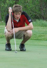 Lansing High's Josh Greene lines up a putt during the Kaw Valley League championships. Greene placed third with a 79 and helped lead LHS to the team championship.