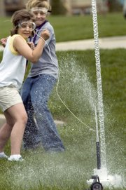A column of water remains after third-graders Kristen Schau and Brandon Schiedel pull the cord to launch their two-liter bottle rocket Friday at Prairie Ridge Elementary.