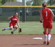THS outfielder Sarah Flaherty attempts to hold on to a catch against Baldwin as shortstop Lindsey Himpel looks on.