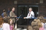 Rev. Mike Bronson of West Haven Baptist Church cuts the ribbon for the church's addition while Chamber of Commerce president Steve Christensen holds the ribbon.