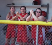 Tonganoxie High seniors Lindsey Himpel, Sarah Flaherty and Amanda Albert cheer from the dugout during their team's 1-0 regional semifinal victory against Baldwin last week in Eudora.