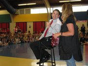 TES assistant principal Ty Poell asks stylist Diane Theno to leave a little on the top during an all-school assembly Wednesday morning. Poell had his head shaved to celebrate students' test scores on the state assessments, taken earlier this spring.