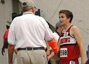 Lansing High sophomore Brandon Craig is congratulated by a meet official after placing sixth in the 3,200-meter run on Friday at the Class 5A state meet.