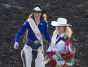 April Brown, left, the 2007 Shrine Rodeo Queen, presents this year's queen, Alyssa Morison, Bonner Springs, with a bouquet of flowers.