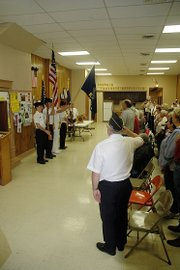 The Shawnee Heights High School junior ROTC provided color guard for Monday's Memorial Day service, which was moved inside the American Legion Hall because of stormy weather. They were shown as participants cited the Pledge of Allegiance to start the service.