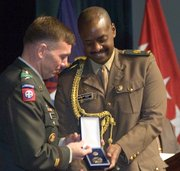 Lieutenant General William B. Caldwell IV (left) presents Maj. Muhozi Kainerugaba of Uganda his badge for completion in the U.S. Army Command and General Staff College at Fort Leavenworth Thursday. Maj. Kainerugaba, the son of President Yoweri Museveni of Uganda. 