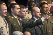 During a group photo session with the graduating class of the U.S. Army Command and General Staff College, Lt. General William B. Caldwell IV (center) points to some of the family members in the audience at the Eisenhower Auditorium at Fort Leavenworth. 