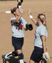 Tonganoxie High senior Lindsey Himpel is congratulated by Olathe North's Marissa Ingle after Himpel made an inning-ending catch in center field during the MO-KAN All-Star Softball Series.