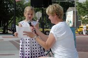 Julia Blanchard, left, receives some assistance from Rita Madl, co-organizer, while reading her Father's Day speech. She was the youngest participant in the essay contest.