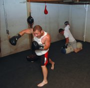 "Steven Adcox, left, and Bill Folsom begin their MMA training session in ""The Dungeon."" Adcox, 155 pounds, is 1-1 in MMA contests and Folsom, 185, is 2-1."