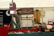 "Mark ""Rooster"" Roster, of Davenport, N.D., peddles wares Friday at the High Plains annual encampment. Roster, a full-time trader, sold clothing, hand-sewn leather goods, and silver adornments made to resemble fashions from as far back as 1700 at the weeklong festival."
