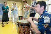 "Keith Hulen, of Bellville, Ill., (right) plays the ""tubano,"" a traditional drum from Ghana, while other music teachers play instruments in rhythm Wednesday during a small group practice in the halls at Delaware Ridge Elementary. The teachers were taking part of a weeklong World Music Drumming workshop."