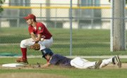 Lawrence's Jake Green dives head-first beneath Post 41 third baseman Ryan Stockman on Friday during the Raiders' 35-0 victory against Tonganoxie at Ice Field. It was the first game of the Kansas American Legion Baseball 2008 Zone 2 Tournament.
