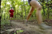 With a canopy of green overhead, runners Nick Foster (left) of Westport and Margaret Hill were part of a group that hit the rolling trails recently at Shawnee Mission Park.