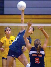 BLHS junior Tara Chumley slams the ball over the net against the Bishop Ward defense of Allison Jenicke (9).