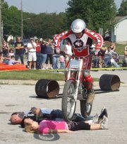 Scott Carpenter, with the Extreme Track and Trial Team, jumps over four crowd participants during his motorcycle demonstration.