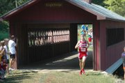 Lansing High junior Brandon Craig crosses a covered bridge on the cross country course at Rim Rock Farm in Lawrence. Craig placed first in the race.
