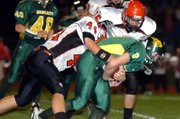 Basehor junior quarterback Brandon Leppke (9) is wrapped up by the Lansing defense Friday night.