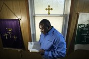 Tyrone Davis reads his favorite Bible scripture in Olivet Church of God where he is a pastor. Davis was released from jail four months ago and is now using his experience to help other young men headed down a talk path.