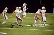 E.J. Fields leads a group of celebrating Chieftains off the field after Tonganoxie High junior Jeremy Elliott recovered a muffed kickoff return in the first quarter of a 29-26 THS victory at Piper on Friday night.