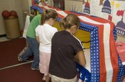 Third-grade students at Tonganoxie Elementary School participated in a mock election Tuesday morning. Inside their voting booths outside their classroom were, from left, Logan Beach, Candler Caldwell, Reagenn Bennett and Kay McKenzie. For more on this story, log on at www.tonganoxiemirorr.com