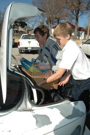 Bryan Ezell, left, and Blake Mayfield, both eighth-graders at Sacred Heart, load a box of food into a car Friday for the Vaughn-Trent Christmas baskets.