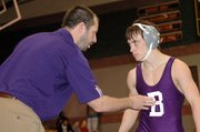 Baldwin High School wrestling coach Kit Harris talks to senior Alan Callahan before his title match Saturday. Callahan placed second in the 112-pound weight class.