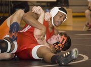 Austen Holloway holds his Bonner Springs opponent to the mat a few seconds before recording a pinfall victory on Thursday night. The Tonganoxie High junior helped the Chieftains to a dual victory against the Braves.