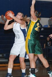 Mill Valley's Nicole Garretson muscles her way to the basket against Basehor-Linwood's Megan Bergstrom.