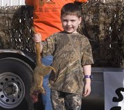 Taylor Whitesell holds up the 1 pound 7 ounce squirrel he helped catch during Saturday's Squirrel Scramble.