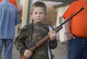 Clayton Bryant, 7, holds the new .22 caliber rifle he won during an auction at Saturday's Squirrel Scramble. The rifle was donated by the Henri Masonic Lodge in Tonganoxie.