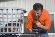 Adam Bryant, owner of Adam's Feed Store, uses an electronic scale to get the exact weight of the squirrels brought in during Saturday's scramble. The top team's squirrels weighed in at 14 pounds, 14 ounces.