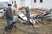 Ben Myers, left, and his grandson Johnathan Myers, inspect the damage done to his barn from an overnight storm.