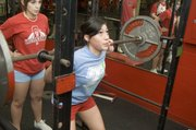 Alex Hauk focuses while practicing her squat recently at Tonganoxie High. The THS girls won the power-lifting team title at Horton on Feb. 7.