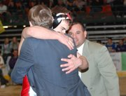 Lansing High sophomore Spencer Blew leaps into coach Ron Averill's arms after winning the 130-pound state championship.