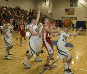 Austin Smith battles Basehor-Linwood defenders for the basketball during Tonganoxie's 68-50 loss in a sub-state final.