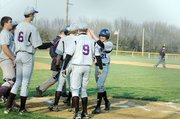 Baldwin High School sophomore Will Von Bargen (No. 21) is greeted by teammates after hitting a home run in the first contest at Ottawa.