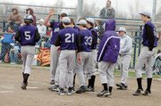 Baldwin High School sophomore Kyle Pattrick (No. 5) is greeted by teammates at home plate after hitting a solo home run Thursday at Wellsville.