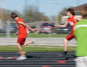 Two Tonganoxie Middle School students prepare to pass the baton in the boys 400 meter relay.