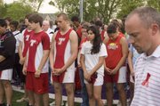 Tonganoxie High track athletes and THS athletics director Brandon Parker, far right, observe a moment of silence at Piper High School in Kansas City, Kan. on Wednesday, May 13, during the Kaw Valley League Meet.