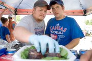 Tim Flory, left, and Chris Chambers of the team Crimson & Blue BBQ Crew, assemble six pieces of their sausage entry into a container that will be delivered to the judges at the McLouth BBQ Blowout. The competition is the Northeast Kansas State BBQ Championship, which is sanctioned by the Kansas City Barbecue Society. The Lawrence team took seventh place overall.